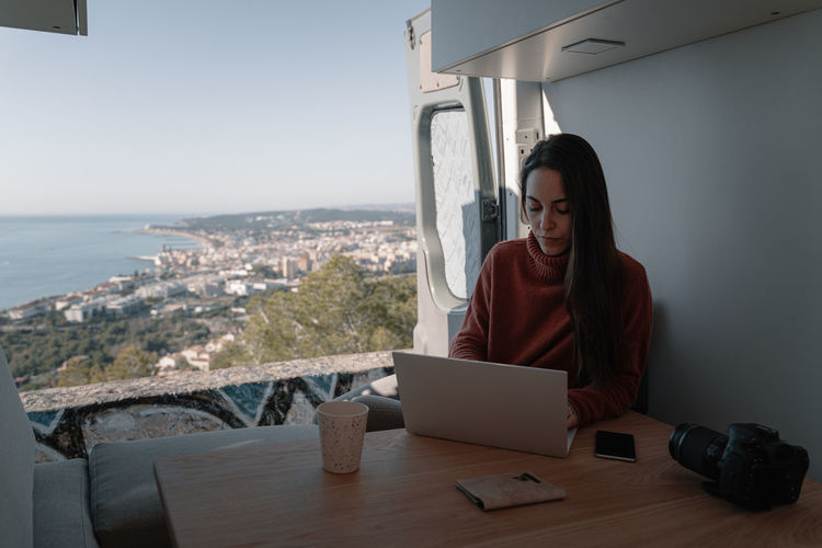 Young woman inside vehicle interior using laptop while sitting on table by sea