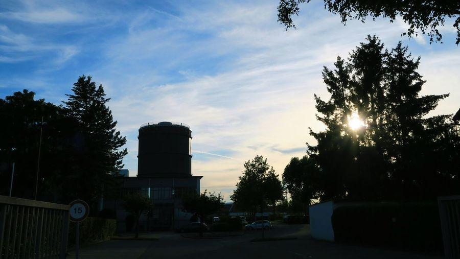 Sun shining through clouds over city