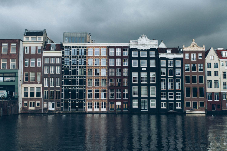 Canal by row houses against sky