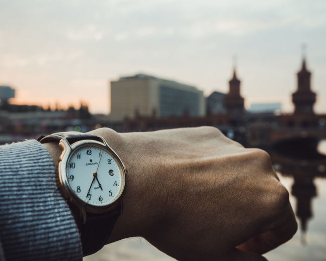 Cropped Image Of Hand Wearing Wristwatch With Oberbaumbruecke In Background