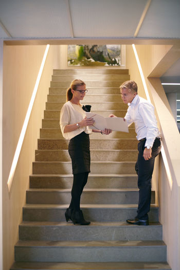 Full length of couple standing on staircase