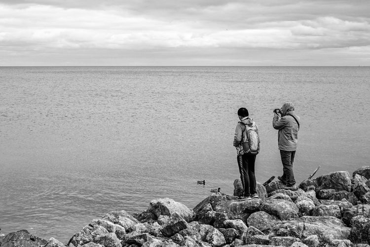 bird watching by the lake Blackandwhite Monochrome Men Togetherness Friendship Sand Full Length Water Standing Shore Horizon Over Water Wave Calm Tranquility