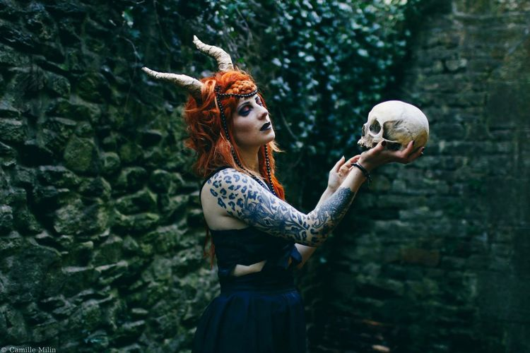 Woman with human skull standing in forest
