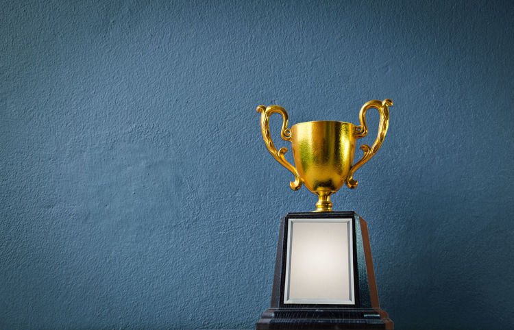 winner trophy champion with copy space blue wall vintage background. champion golden trophy The reward for a successful year. copy space business and sport competition concept idea Champion First Golden Achievement AWARD Best  Champ Competition Copy Space Cup First Place  Game Golden Trophy Honor Leadership Metallic No People Prize Reward Space Success Trophy Victory Winner Trophy Winning