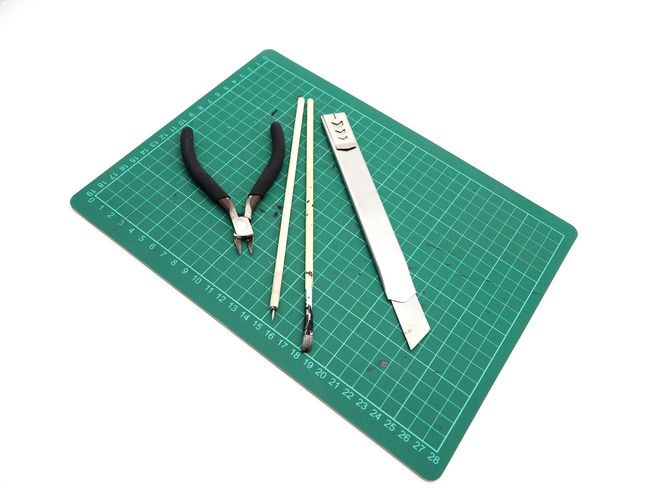 Tools with green cutting mat for model kit isolated on white background. Close-up Copy Space Cut Out Directly Above Education Equipment Green Color High Angle View Indoors  Metal No People Paper Security Still Life Studio Shot Technology Two Objects White Background