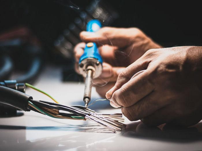 Close-up of man repairing equipment