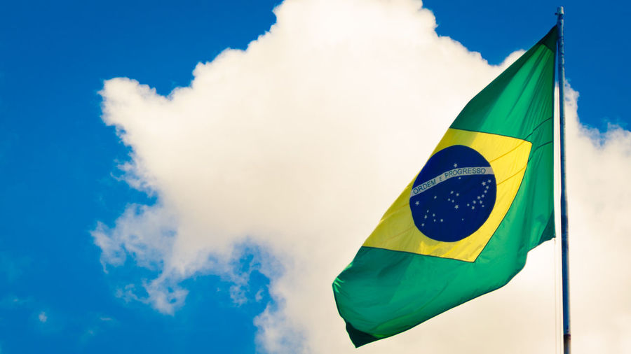 Low Angle View Of Brazilian Flag Fluttering Against Sky