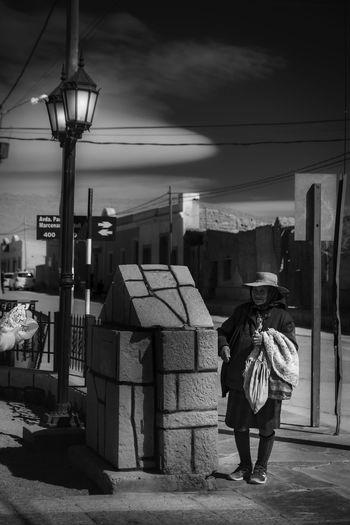 Rear view of women walking on street amidst buildings