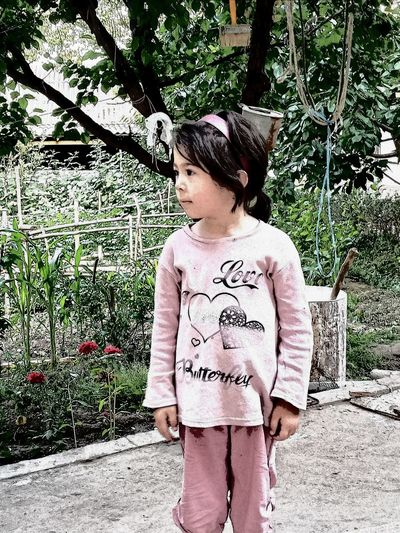 Low section of girl standing against tree