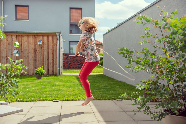 Woman jumping against plants