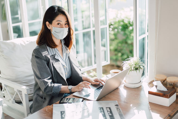 Portrait of businesswoman wearing mask sitting at cafe