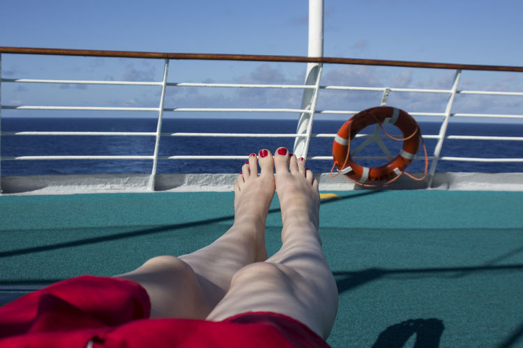 Low section of woman relaxing on deck