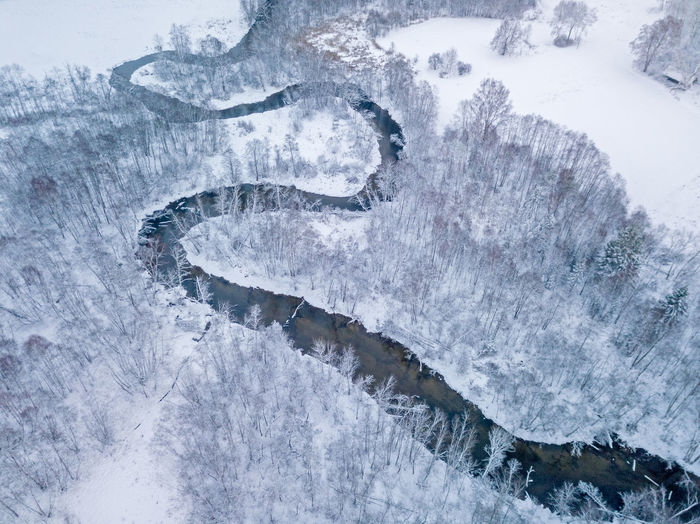 High angle view of stream amidst snowy land