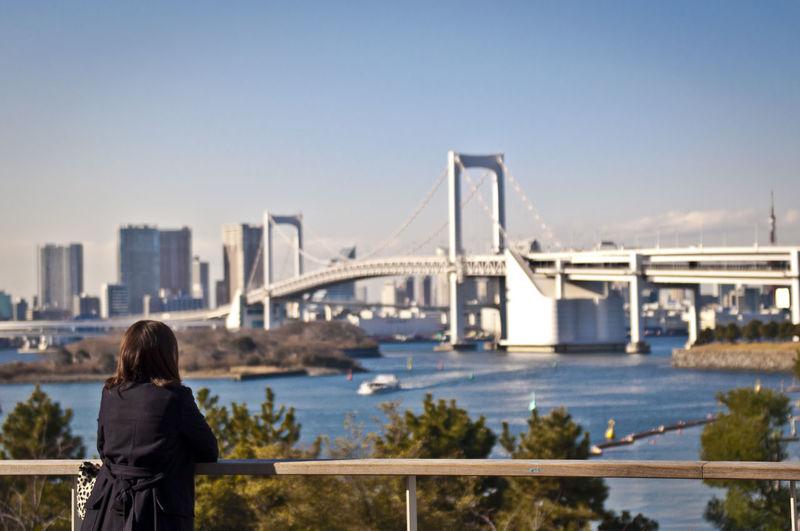 Rear view of woman looking at suspension bridge