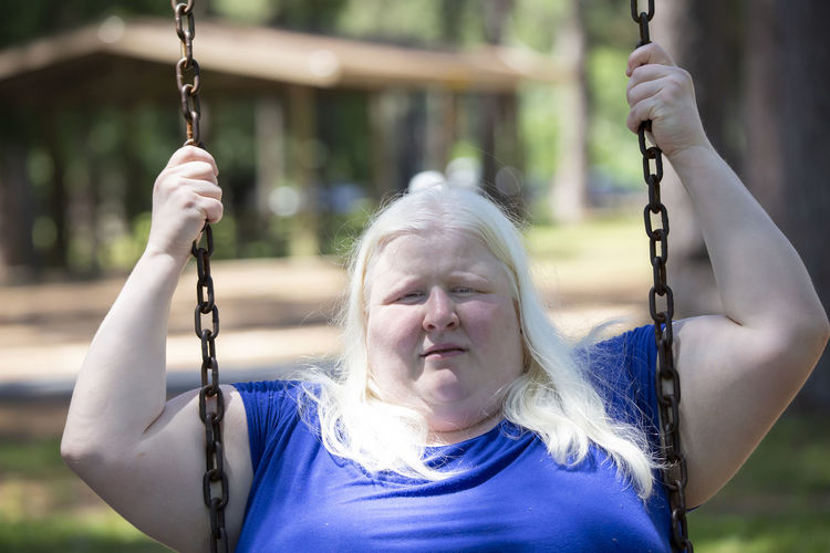 Portrait of overweight woman on swing at playground
