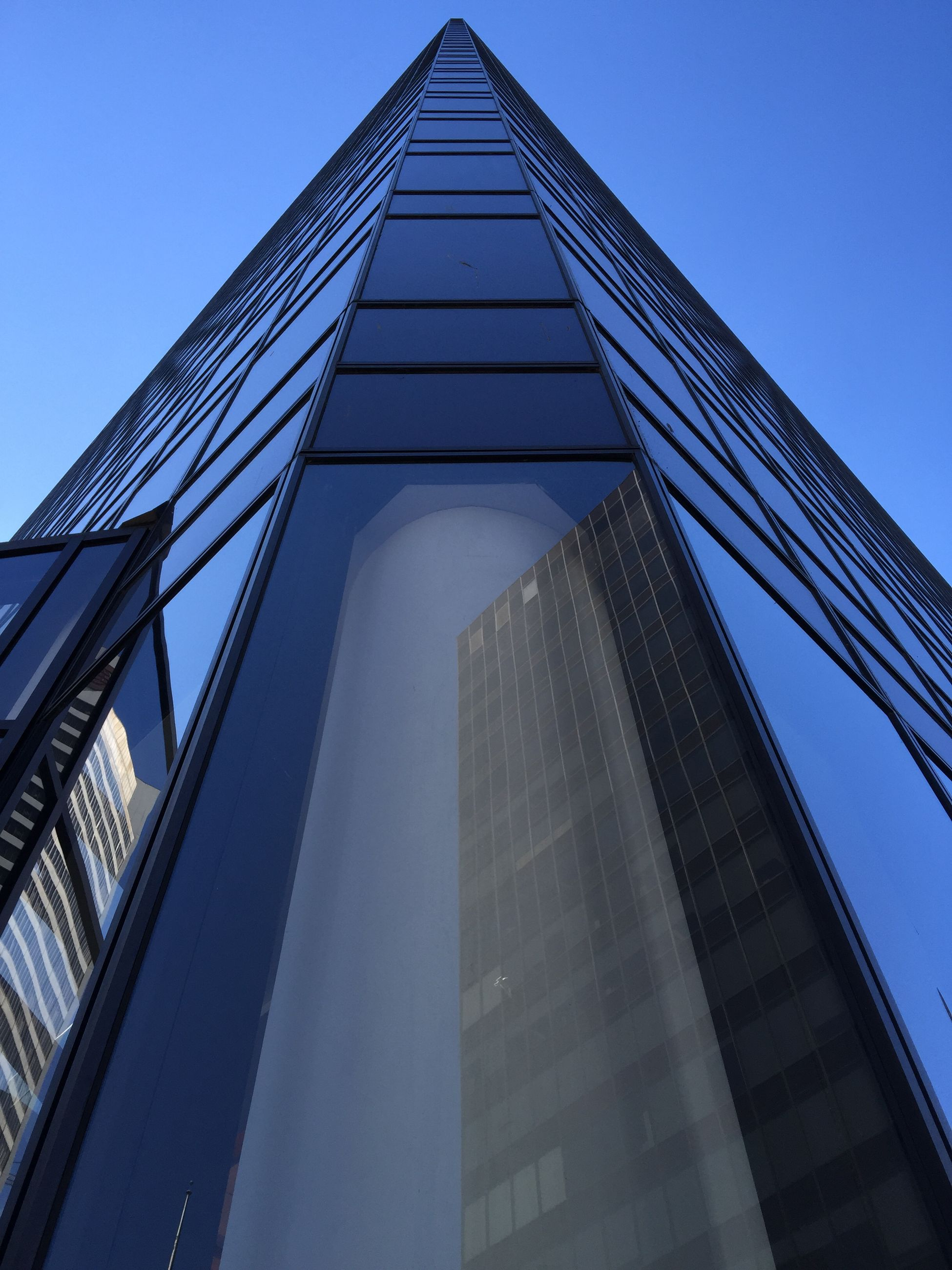 architecture, built structure, low angle view, building exterior, clear sky, blue, modern, reflection, office building, glass - material, building, city, tall - high, tower, skyscraper, day, sky, outdoors, no people, window