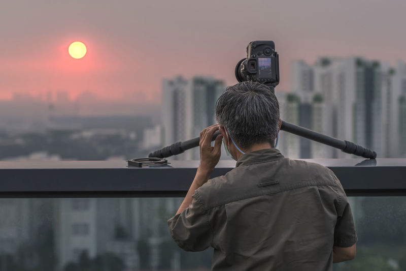 Rear view of man photographing against cityscape during sunset