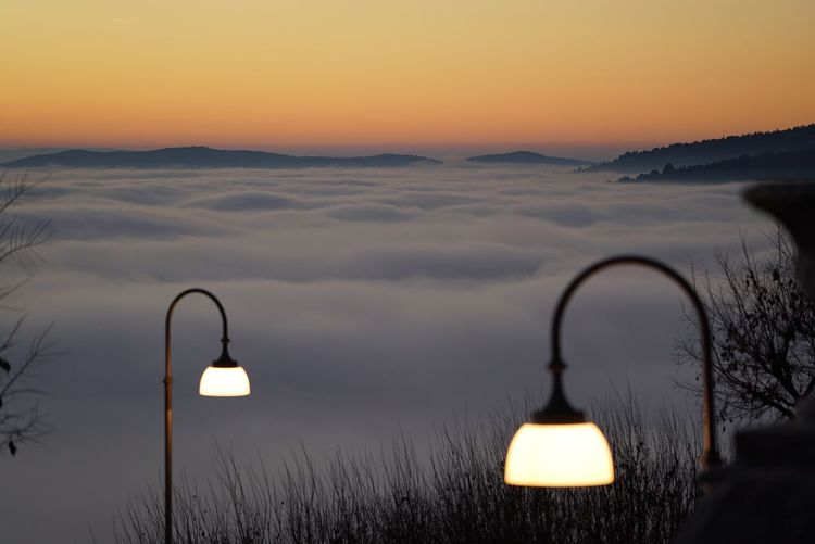AERIAL VIEW OF FOG AGAINST MOUNTAIN RANGE AT SUNSET