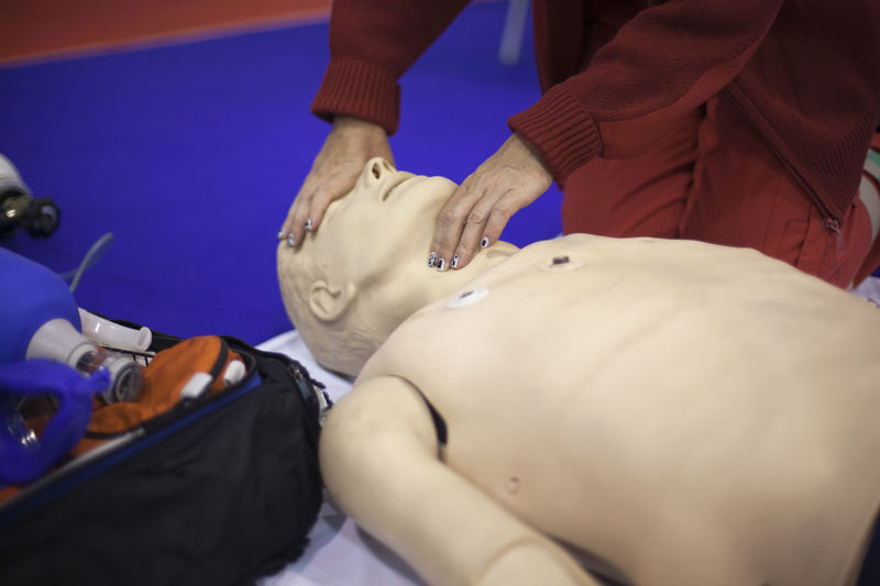 Midsection of man practicing on cpr dummy at hospital