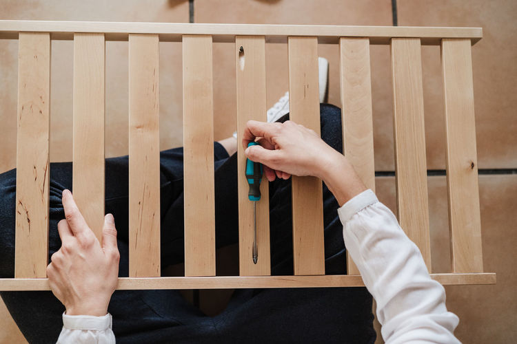 Low section of woman holding screw driver with furniture