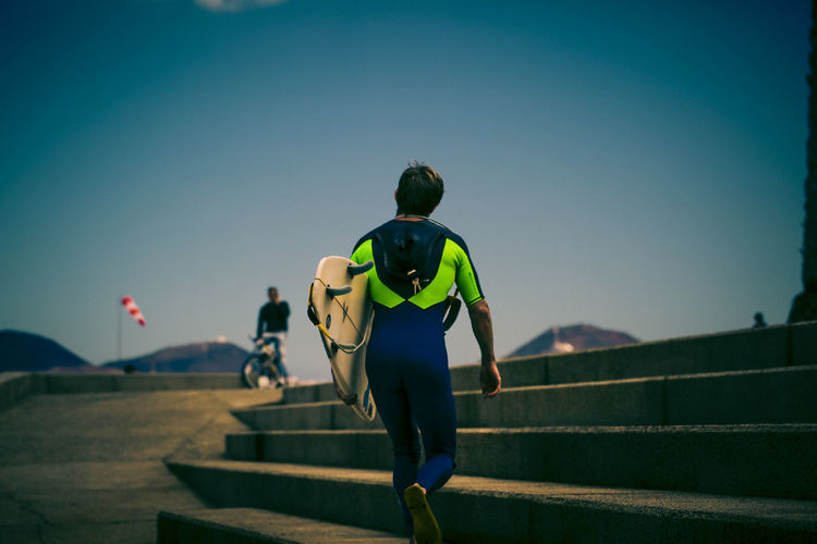 Rear View Of Man In Wetsuit Carrying Surfboard