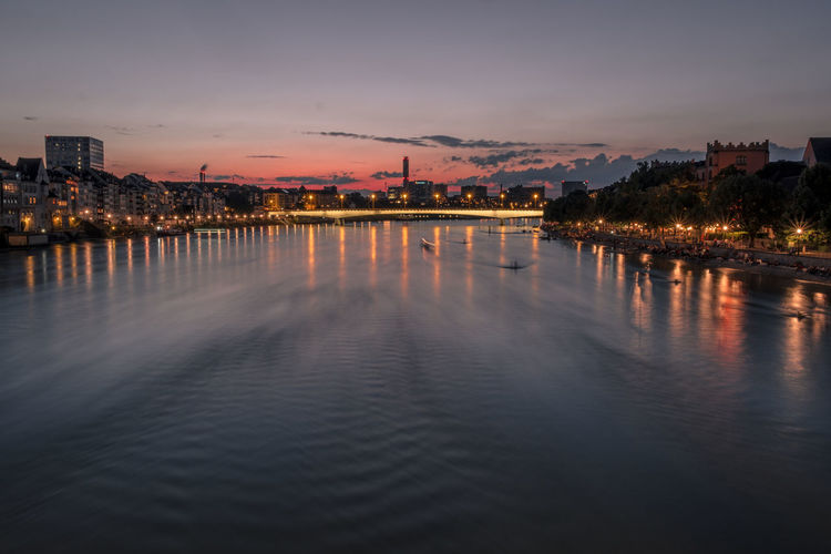 River by illuminated city against sky at sunset
