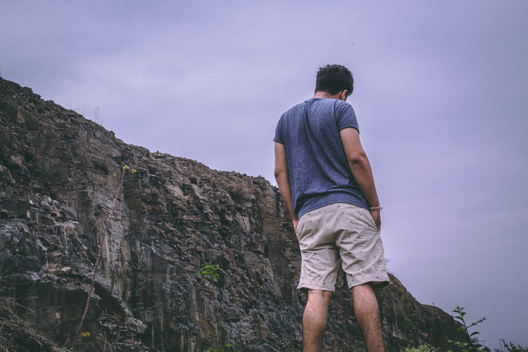 Rear view of man standing by rock against sky