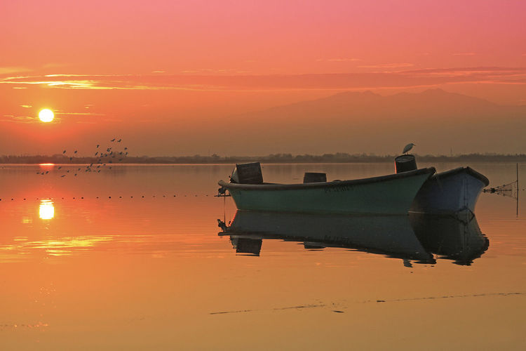 Beauty In Nature Fishing Boat Idyllic Mode Of Transportation Nature Nautical Vessel No People Orange Color Reflection Scenics - Nature Sea Sky Standing Water Sunset Tranquil Scene Tranquility Transportation Water Waterfront
