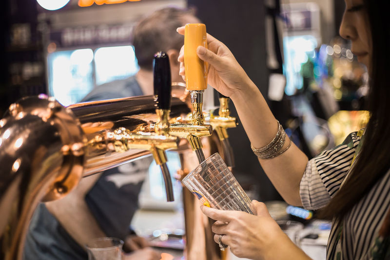 Beer Business Alcohol Arts Culture And Entertainment Close-up Focus On Foreground Hand Holding Human Body Part Human Hand Illuminated Indoors  Lifestyles Marketing Midsection Music Musical Instrument Occupation People Playing Real People Saxophone Selective Focus Skill