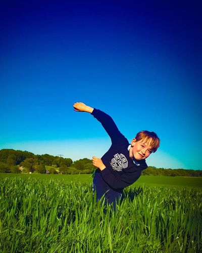 Boy playing on field against clear blue sky