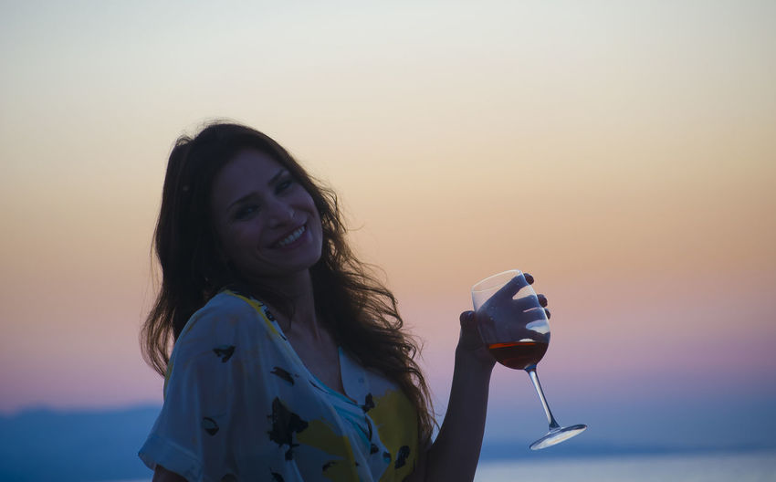 Young Woman Drinking Red Wine At Sunset