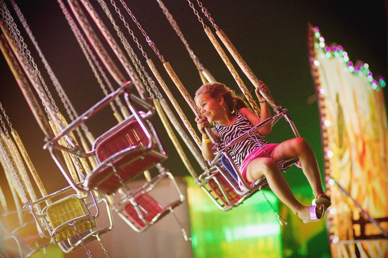 Smiling girl looking away while sitting on chain swing ride