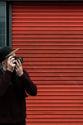 Midsection of man photographing while standing against shutter