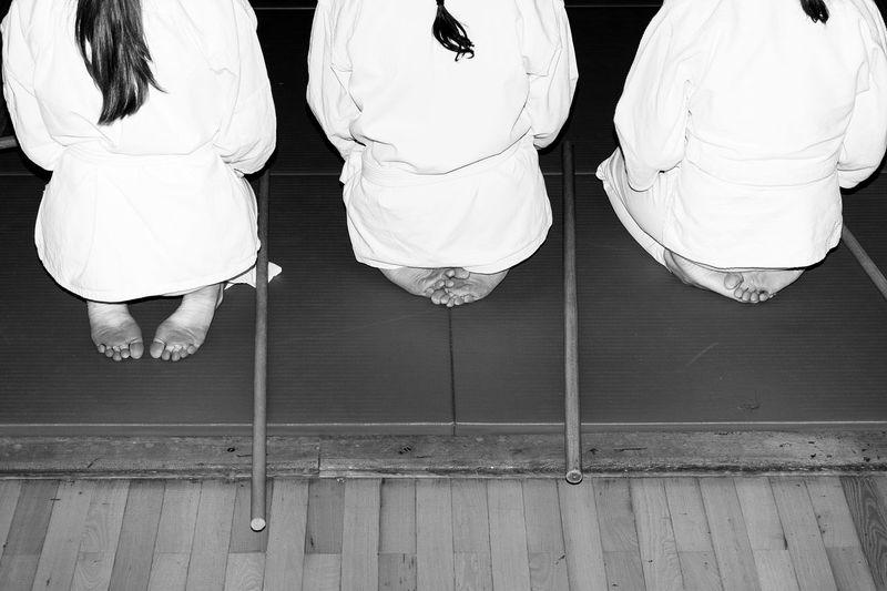 Three female aikido students sitting in seiza on tatami with wooden jo sticks near Back Discipline To Improve Foot Japan KimonoStyle Martial Arts Seiza Tatami Aikido Practice Aikido Serbia Aikido Students Aïkido Behind Blackandwhite Photography Girls Hairstyle Hands On Knees Jo Kimono Girl Martialarts Ponny Tail Sticks Tori White Belt White Kimono