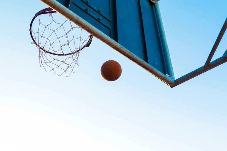 Low angle view of basketball at hoop against clear sky