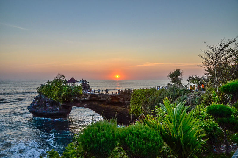 Tanah lot by sea against sky during sunset