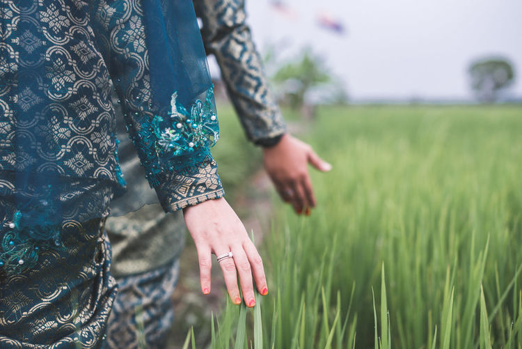 Happy newlywed couple walking by green paddy field while touching the plant, shallow depth of field, selective focus on bride hand with ring. Adult Blur Close-up Couple Day Green Color Hand Human Body Part Nature Outdoors Paddy People Ring Rural Scene Shallow Depth Of Field Wedding