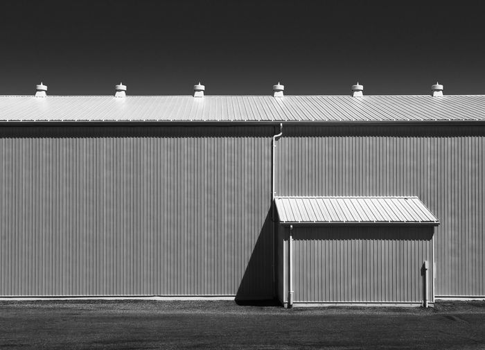 Architectural details of a agricultural shed against a blue sky taken in a minimalist style.