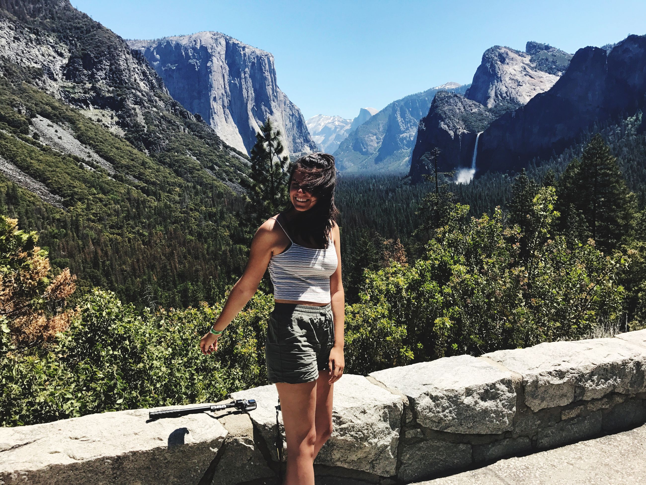 real people, leisure activity, young adult, mountain, lifestyles, young women, casual clothing, nature, front view, one person, rock - object, standing, beauty in nature, outdoors, day, full length, tree, hot pants, happiness, sunlight, beautiful woman, scenics, looking at camera, smiling, sky, clear sky