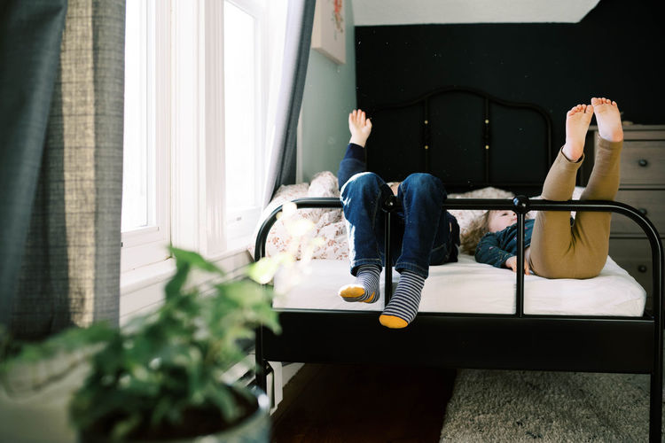 Low section of man sitting on sofa at home