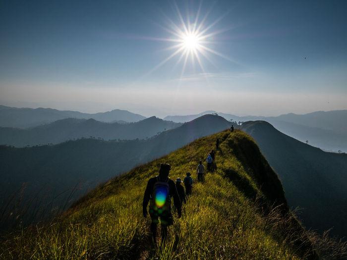 Rear view of people walking on ridge against sky