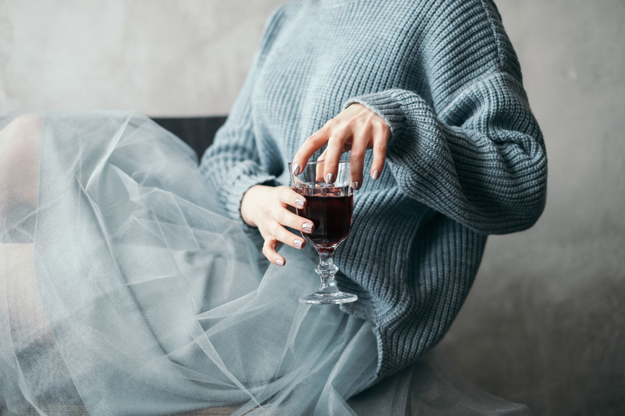 Midsection of woman having red wine at home