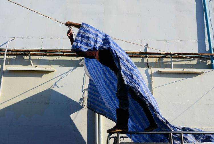Man applying tarpaulin on rope