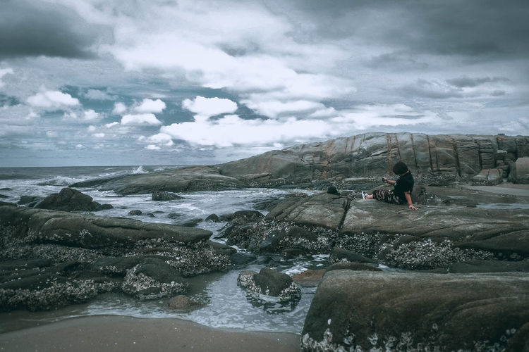Woman sitting on rock at beach against cloudy sky