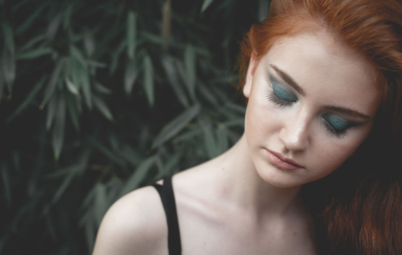 Close-up of young woman with make-up against plants
