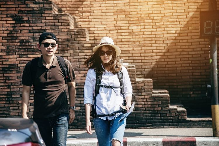 Portrait of couple walking on road against wall