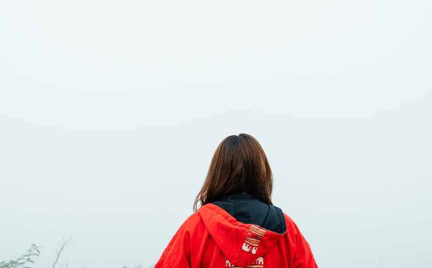 Rear view of woman standing against clear sky