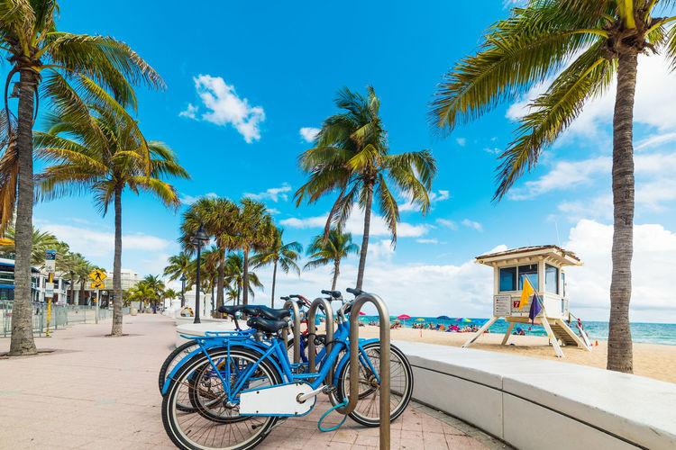 Bicycles on beach against blue sky