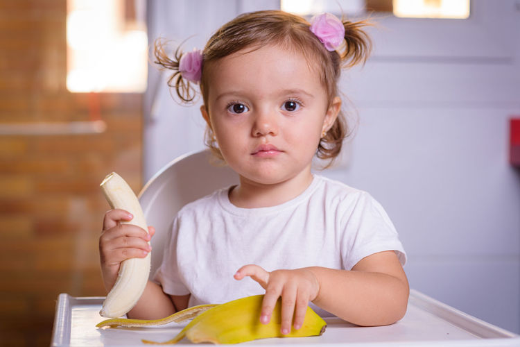 Cute baby girl with banana on high chair at home