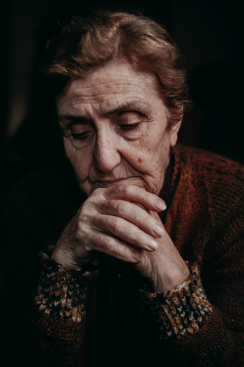 Close-Up Of Sad Senior Woman Against Black Background